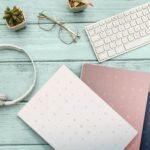 Woman home office desk workspace with laptop, headphones  cactus in pastel blue wooden. Flat lay, top view. stylish female concept